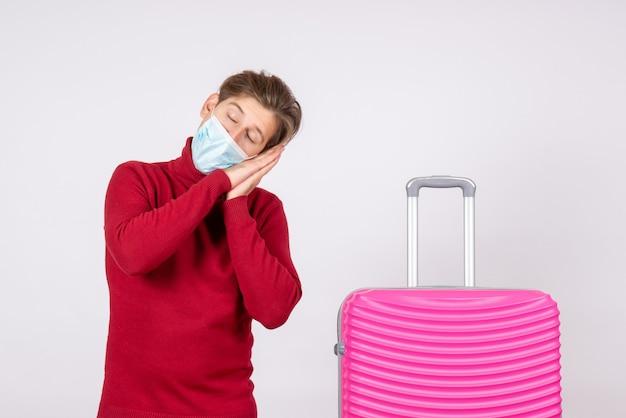 Вид спереди молодого мужчины в маске с розовой сумкой, спящей на белой стене