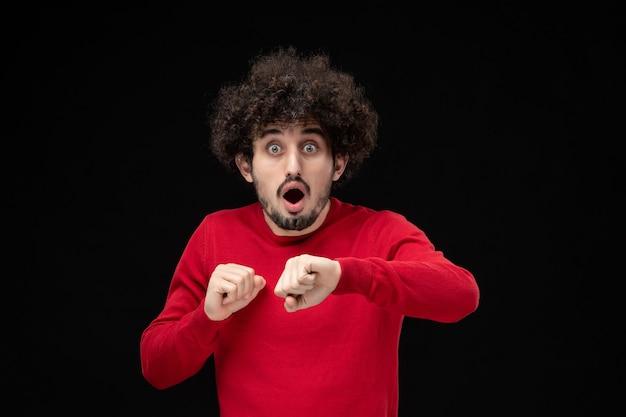 黒い壁で時間をチェックする赤いシャツの若い男性の正面図