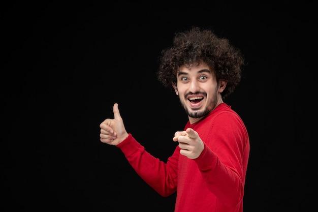 검은 벽에 흥분을 느끼는 빨간 셔츠를 입은 젊은 남성의 전면 모습
