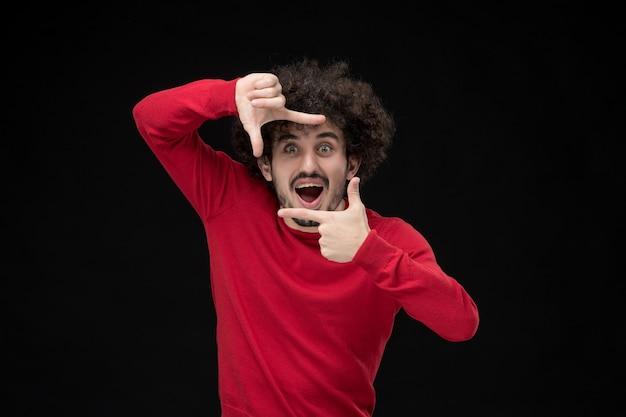 黒い壁に興奮している赤いシャツの若い男性の正面図