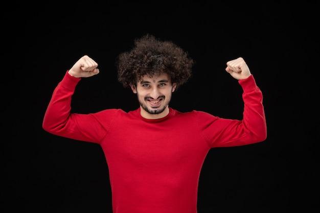 黒い壁に曲がって赤いシャツを着た若い男性の正面図