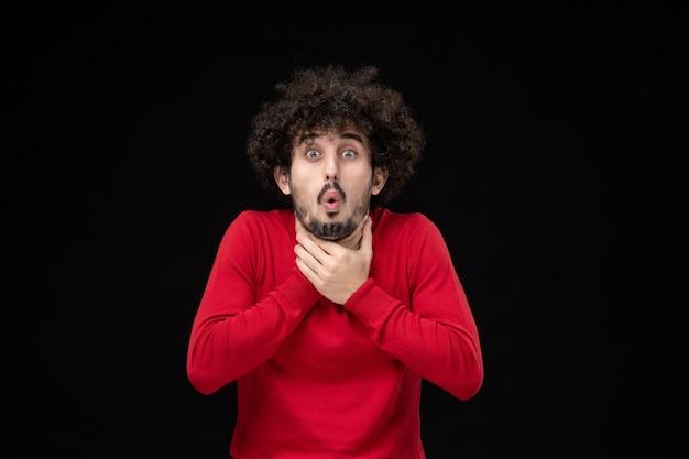 黒い壁に喉の痛みを持っている赤いシャツの若い男性の正面図