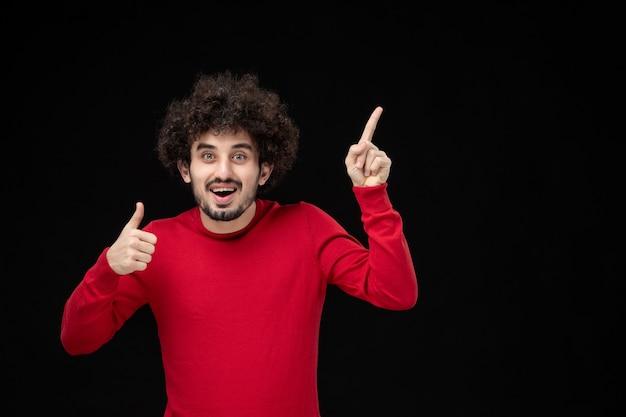 검은 벽에 빨간 셔츠에 젊은 남성의 전면 보기