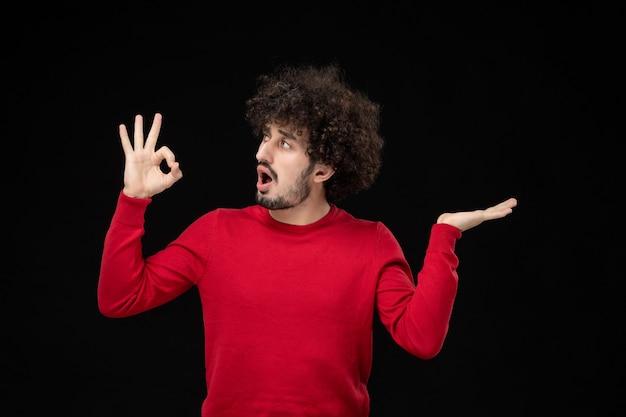 黒い壁に赤いシャツを着た若い男性の正面図