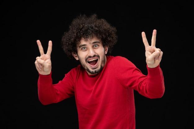 Вид спереди молодого мужчины в красной рубашке на черной стене
