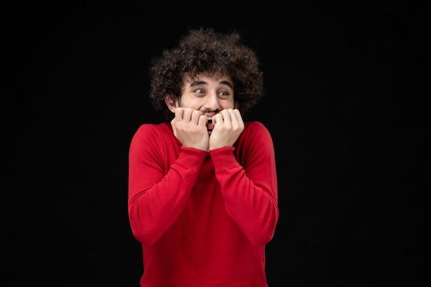 검은 벽에 빨간 스웨터를 입은 젊은 남성의 전면 모습