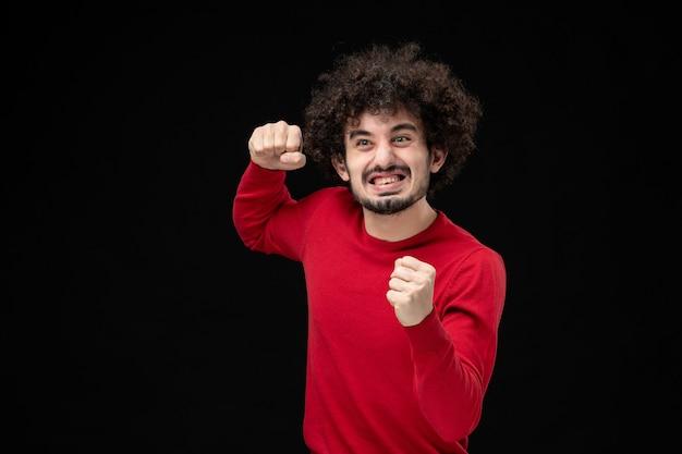 Вид спереди молодого мужчины в красном свитере на черной стене