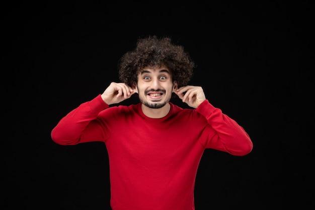 黒い壁に赤いセーターを着た若い男性の正面図