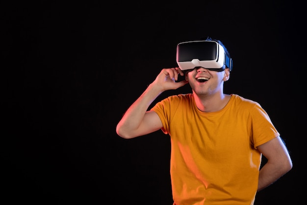 Вид спереди молодого мужчины, играющего в виртуальную реальность на темной стене