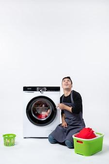 흰 벽에 세탁기를 위해 더러운 옷을 준비하는 젊은 남성의 전면 모습