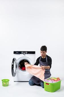 Вид спереди молодого мужчины, готовящего грязную одежду для стирки на белой стене