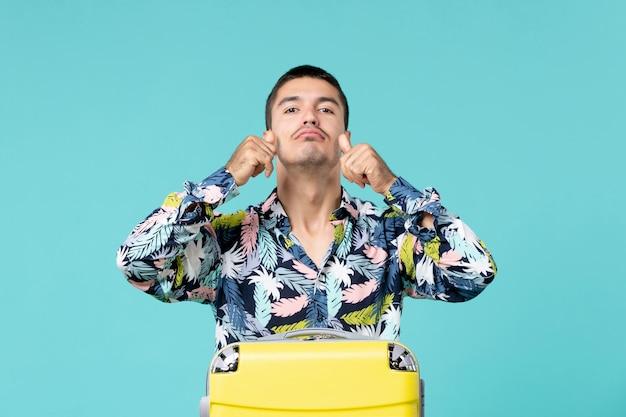 青い壁で長旅の準備をしている若い男性の正面図