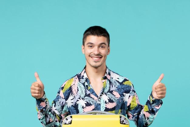 水色の壁で長旅の準備をしている若い男性の正面図