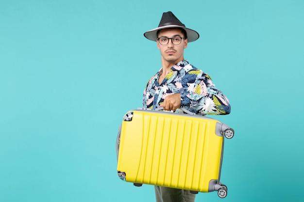 旅行の準備と青い壁に彼のバッグを保持している若い男性の正面図