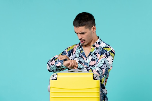 青い壁に時間をチェックする彼の黄色いバッグで旅行の準備をしている若い男性の正面図