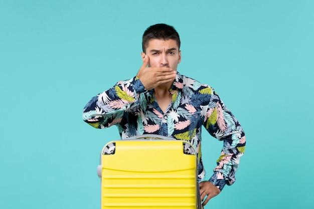 青い壁に彼の口を覆う彼の黄色いバッグで旅行の準備をしている若い男性の正面図