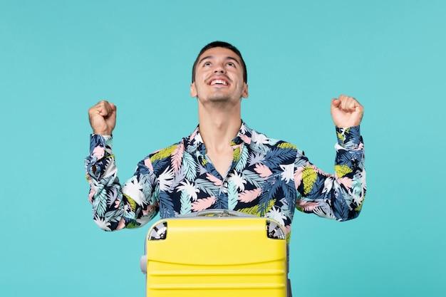 青い壁に興奮している彼の黄色いバッグと旅行の準備をしている若い男性の正面図