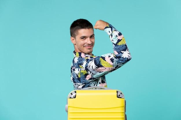 青い壁に曲がっている彼の黄色いバッグで旅行の準備をしている若い男性の正面図