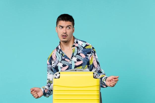 青い壁に彼の黄色いバッグを持って旅行の準備をしている若い男性の正面図