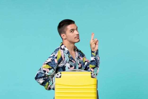 青い表面に彼の黄色いバッグを持って旅行の準備をしている若い男性の正面図