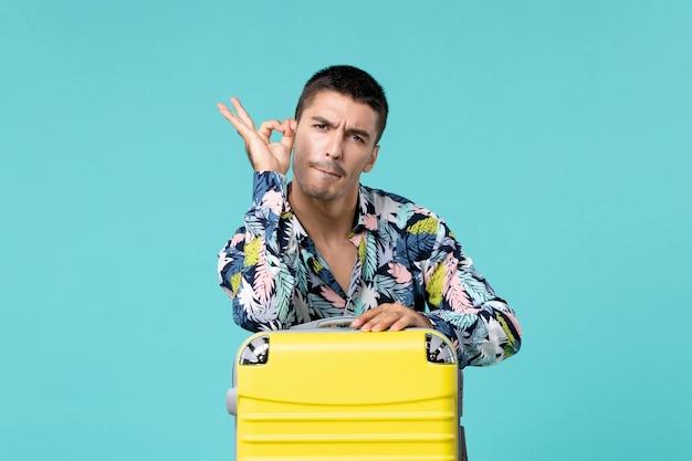 水色の壁に彼の黄色いバッグを持って旅行の準備をしている若い男性の正面図