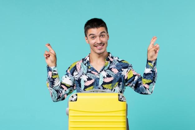 파란색 벽에 그의 노란색 가방으로 여행을 준비하는 젊은 남성의 전면보기