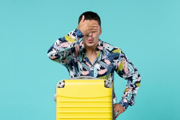 밝은 파란색 벽에 노란색 가방과 함께 여행을 준비하는 젊은 남성의 전면보기