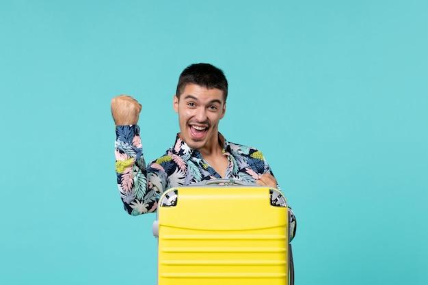그의 노란색 가방이 파란색 벽에 기뻐하는 여행을 준비하는 젊은 남성의 전면보기