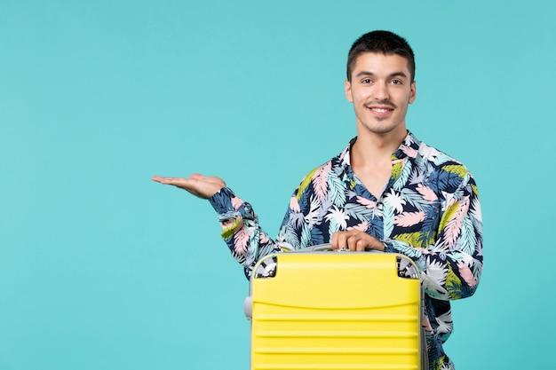 青い壁に笑みを浮かべて彼の黄色いバッグと旅行の準備をしている若い男性の正面図