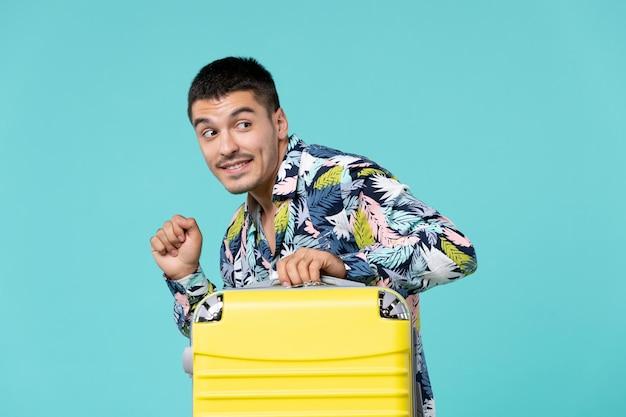 가방과 함께 휴가를 준비하고 파란색 벽에 조용히 떠나는 젊은 남성의 전면보기
