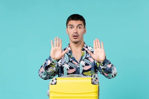 青い壁に黄色のバッグと休暇の準備をしている若い男性の正面図