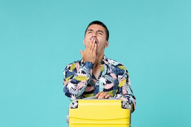 青い壁に黄色いバッグあくびをして休暇の準備をしている若い男性の正面図
