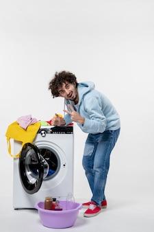 흰 벽에 더러운 옷을 세탁기에 넣는 젊은 남성의 전면 보기
