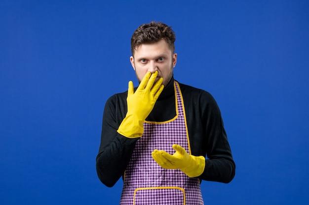 파란색 벽에 서 있는 코 앞에 손을 대는 젊은 남성의 전면 모습