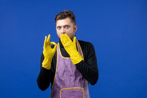 파란색 벽에 오키 사인을 하는 입에 손을 대고 있는 젊은 남성의 전면 모습