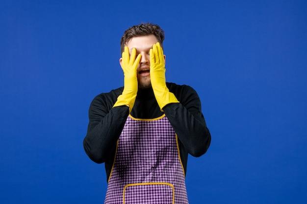 파란색 벽에 서 있는 그의 얼굴에 손을 대고 있는 젊은 남성의 전면 모습