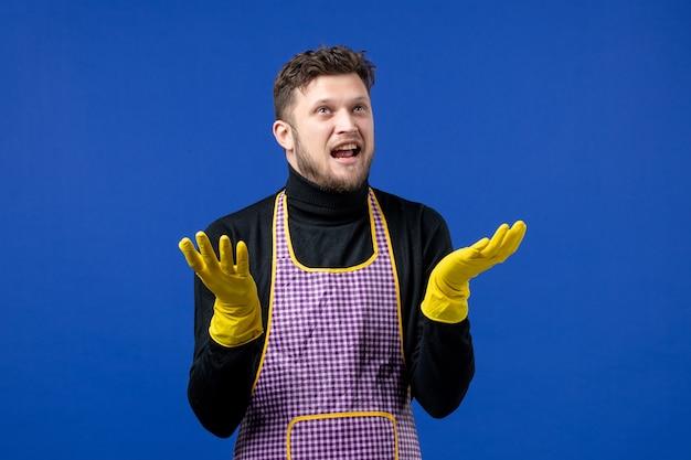 파란색 벽에 서 있는 손을 올리는 젊은 남성의 전면 보기