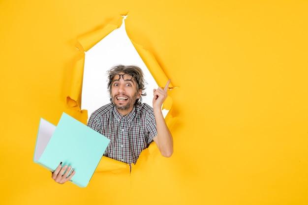 黄色の壁に緑のファイルを読んで若い男性の正面図