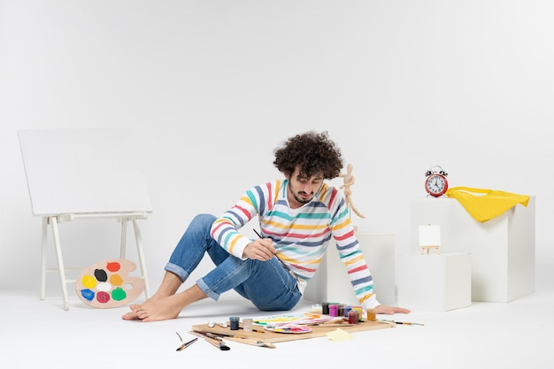 흰 벽에 페인트와 그림 주위에 앉아 젊은 남성의 전면 보기