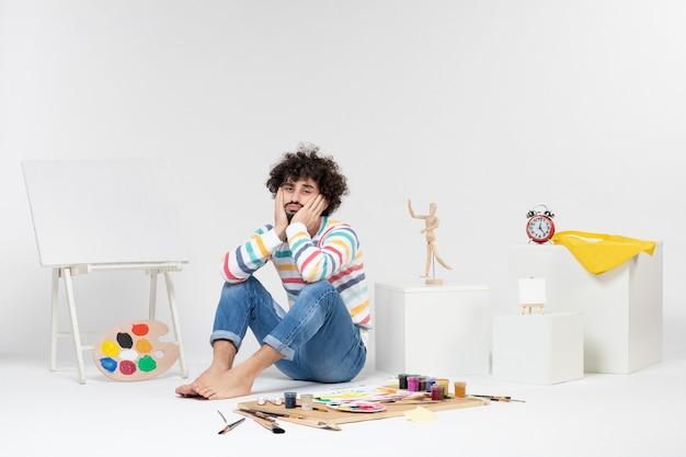 白い壁の絵の具や絵の周りに座っている若い男性の正面図