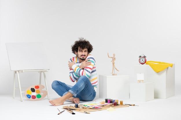 Вид спереди молодого мужчины, сидящего вокруг красок и рисунков на белой стене