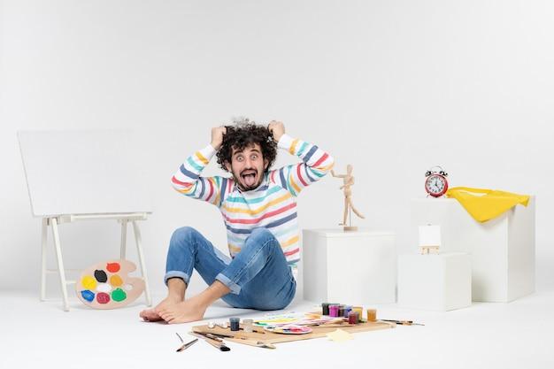 Вид спереди молодого мужчины, сидящего вокруг красок и рисунков, рвущих волосы на белой стене