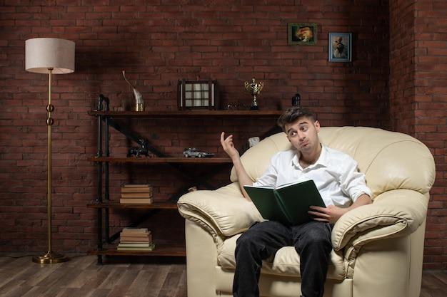 ソファに座って、部屋のオフィス家具の仕事の家のビジネスの中でメモを書いている若い男性の正面図