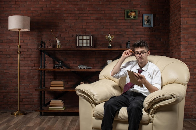 部屋の学生の専門的な仕事のオフィスの仕事の中でメモを書くソファに座っている若い男性の正面図