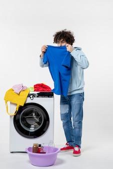洗濯機からきれいな服を取り出し、白い壁に匂いを嗅ぐ若い男性の正面図