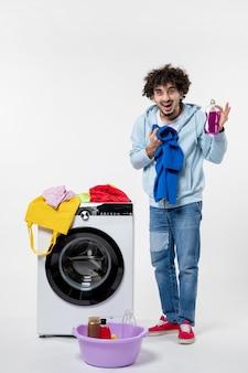 흰 벽에 있는 세탁기에서 깨끗한 옷을 꺼내는 젊은 남성의 전면 모습