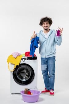 Вид спереди молодого мужчины, вынимающего чистую одежду из стиральной машины на белой стене