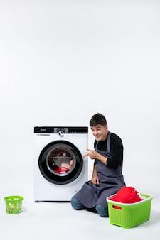 白い壁に洗濯機の助けを借りて服を洗う若い男性の正面図