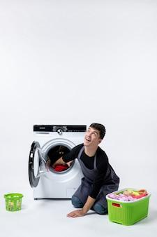 Вид спереди молодых мужчин, стирающих одежду с помощью стиральной машины на белой стене