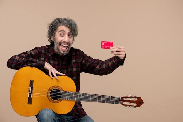 분홍색 벽에 빨간 은행 카드를 들고 기타와 함께 젊은 남성의 전면 보기